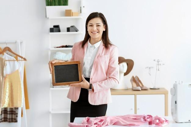 アトリエにミニ黒板を持つ若い女性のポートレート。小規模事業主