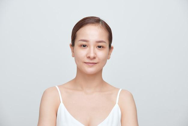 白い背景の上にメイクアップのない若い女性の肖像画