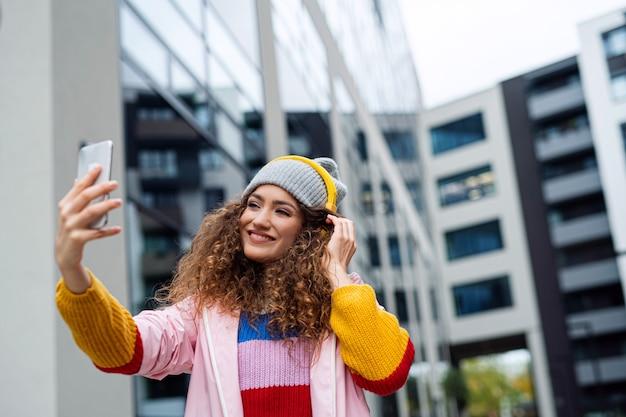 Портрет молодой женщины с смартфоном, делающим видео на открытом воздухе на улице, концепция tik tok.
