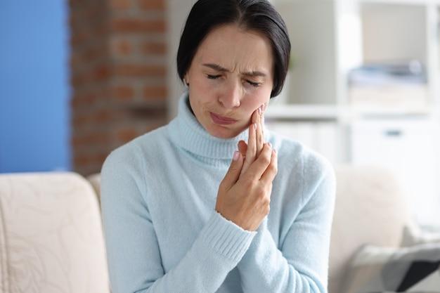 소파에 앉아 있는 동안 치통을 가진 젊은 여성의 초상화. 플럭스의 원인과 증상