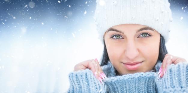 Портрет молодой женщины с свитером и крышкой зимней одежды.