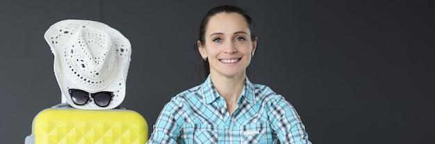 Портрет молодой женщины с желтым чемоданом и шляпой, переезжающей за границу