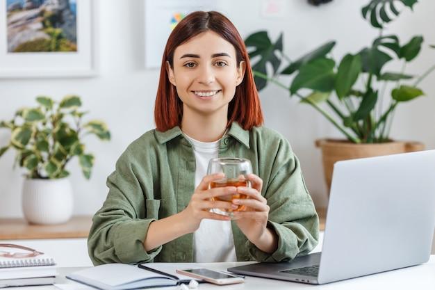 Портрет молодой женщины, работающей дома с ноутбуком расслабленная бизнес-леди, держа чашку чая