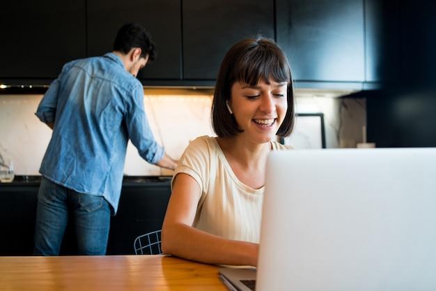 Портрет молодой женщины, работающей с ноутбуком из дома, пока мужчина чистит кухню на заднем плане.