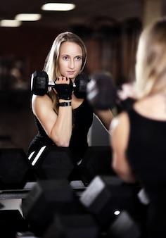 ジムでの若い女性のトレーニングの肖像画