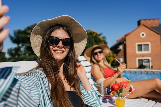 プールサイドで日光浴を楽しんでいる若い女性の肖像画。