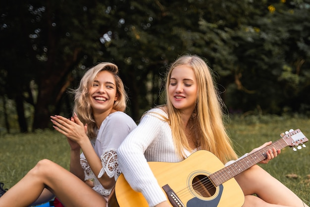 Портрет молодой женщины, сидя в парке на открытом воздухе и играть на гитаре