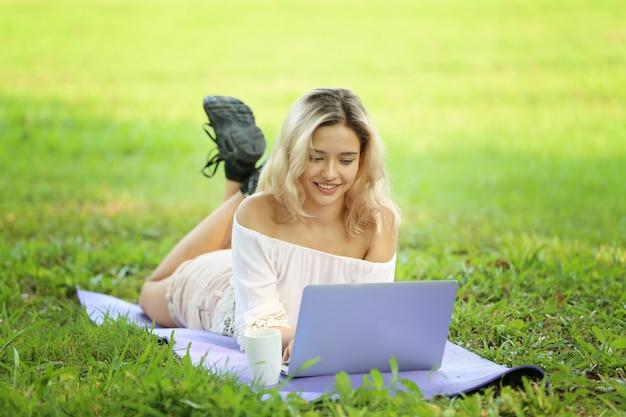 草の上に横たわっているときにラップトップを使用して若い女性の肖像画。