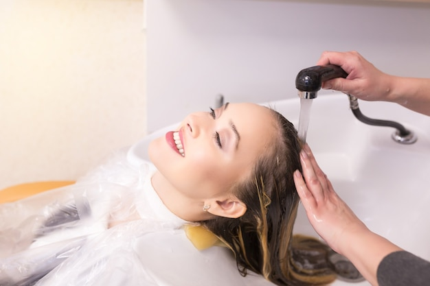 ヘアカラーの後に美容院で髪を洗う若い女性の肖像画