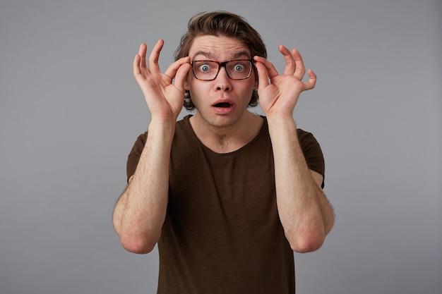 안경을 쓴 젊은 궁금해 잘 생긴 남자의 초상은 기본 티셔츠를 입고 회색 배경 위에 서서 넓게 미소 짓고, 입을 벌리고 물마루 안경을 본다.
