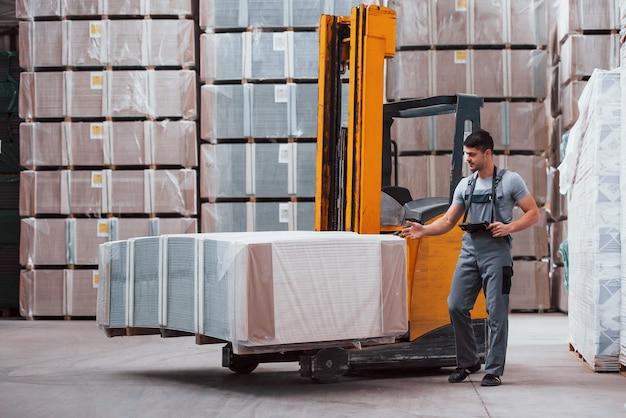 Портрет молодого работника в униформе, который находится на складе возле погрузчика.