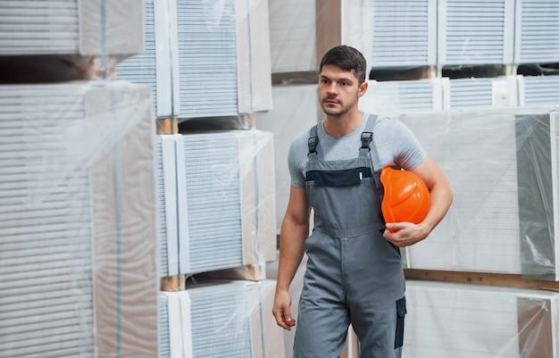 倉庫にあるunifrormの若い労働者の肖像画。