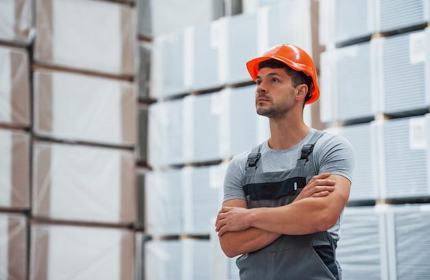 Портрет молодого работника в униформе, которая находится на складе.