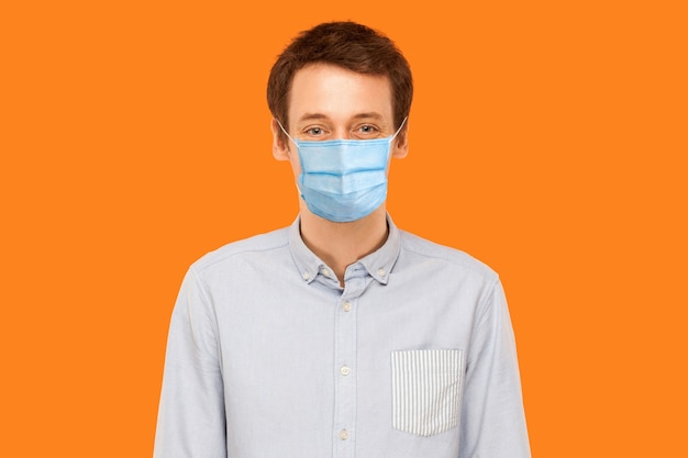 立って、カメラの笑顔を見ているサージカルマスクを持つ若い労働者の男の肖像画。ヘルスケアと医学の概念。オレンジ色の背景に分離された屋内スタジオショット。