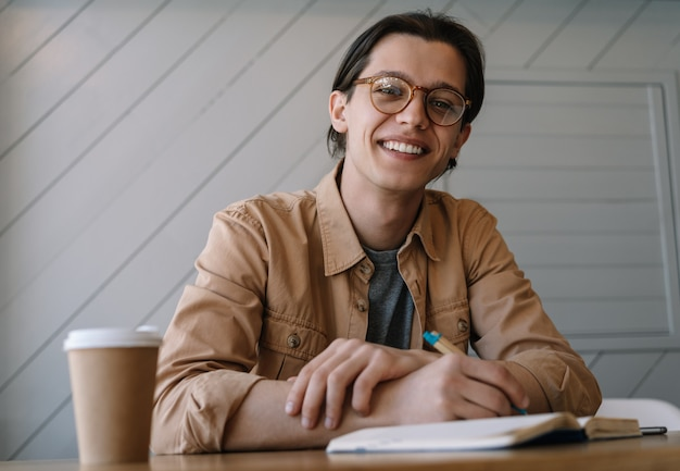 Портрет молодой писатель заметок в блокноте, улыбаясь. фрилансер работает из дома