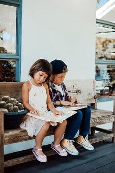 彼らが昼間に公園のbecnhに座って科学的な本を読んでいる若者とかわいい子供たちの肖像画。