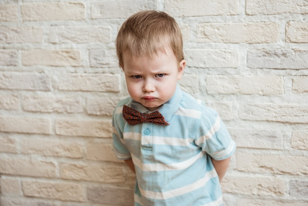 Portrait of an offended child boy on a brick background