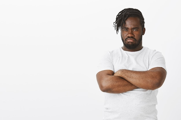 Portrait of offended guy with braids posing against the white wall
