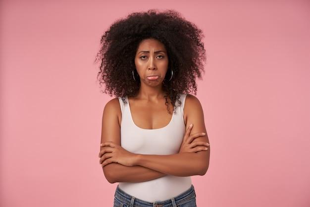Ritratto di giovane donna dalla pelle scura offesa con acconciatura casual in piedi sul rosa con le mani giunte, con le labbra increspate e il viso sconvolto