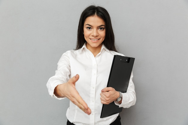 Portrait of office woman with long dark hair wearing white shirt smiling and giving hand for shaking while holding folder with documents, isolated over gray background