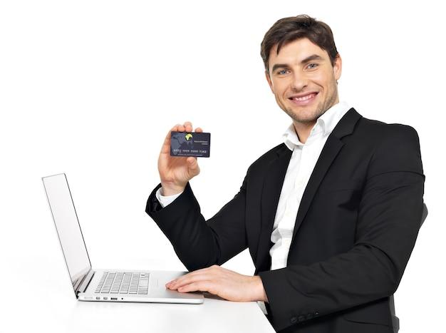 Ritratto di impiegato con laptop e carta di credito seduto sul tavolo isolato su bianco.