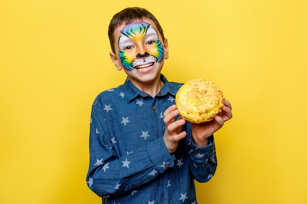 Portrait oh little boy in casual shirt with paint on face, holding sweet donut isolated on yellow wall.
