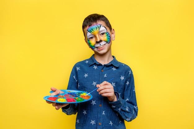 顔にペンキ、黄色の壁に分離されたガッシュパレットとカラフルな虎のカジュアルなシャツの肖像画ああ小さな男の子
