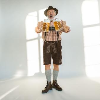 Ritratto di uomo anziano oktoberfest con cappello, indossando i tradizionali abiti bavaresi. maschio full-length girato in studio su sfondo bianco. la celebrazione, le vacanze, il concetto di festival. bevendo birra.