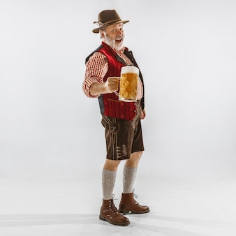 Portrait of oktoberfest senior man in hat, wearing the traditional bavarian clothes. male full-length shot at studio on white background. the celebration, holidays, festival concept. drinking beer.