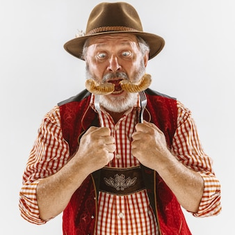 Portrait of oktoberfest senior man in hat, wearing the traditional bavarian clothes. male full-length shot at studio on white background. the celebration, holidays, festival concept. eating sausages.