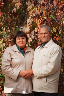 Portrait of an old caucasian couple in the autumn forest of the park, husband and wife smiling and holding hands.