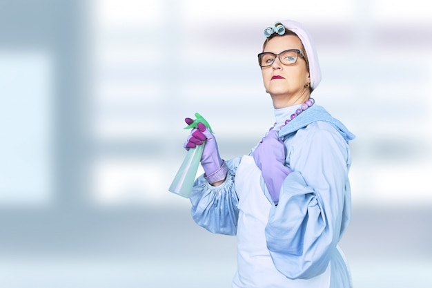 Portrait of old cleaning woman in apron with dust cleaning brush isolated on blue background. special uniform and professional equipment for cleaning