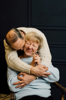 Portrait of old couple wife and husband hugging and smiling. dark blue background. happy lovers on retirement. stop ageism. . high quality photo