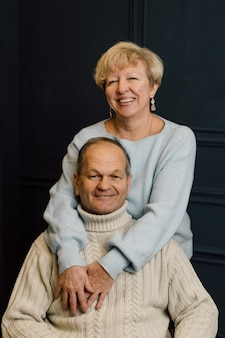 Portrait of old couple wife and husband hugging and smiling. dark blue background. happy lovers on
