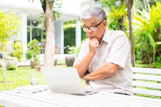 Portrait of old elderly asian man using a computer laptop in the backyard for learning new skill after retired. concept of no ageism and not be late for learning.