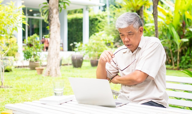 Portrait of old elderly asian man using a computer laptop