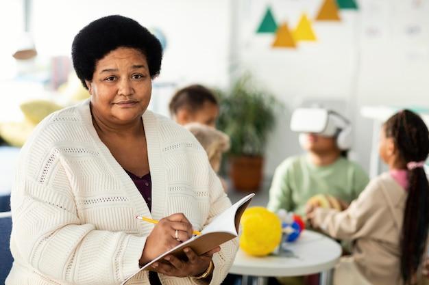 Portrait of old female teacher in class