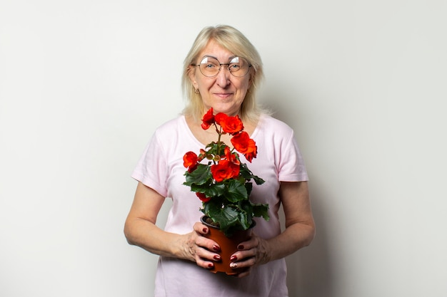 Portrait of an old friendly woman in a casual t-shirt and glasses holding a room flower on an isolated light wall. emotional face. the concept of plant care, home garden