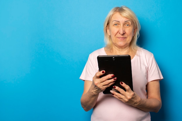 Portrait of an old friendly woman in a casual t-shirt holding a tablet in her hands and looking at the screen on an isolated blue wall. emotional face