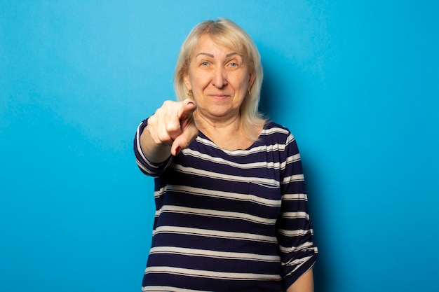 Portrait of an old friendly woman in a casual t-shirt points a finger at the viewer on an isolated blue wall. emotional face. concept are you next