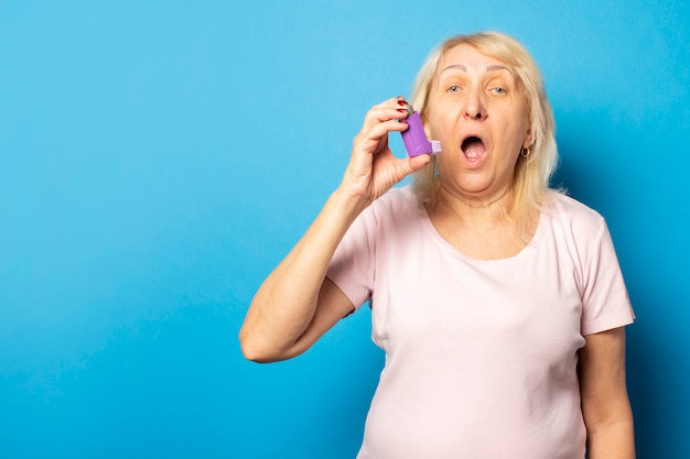 Portrait of an old friendly woman in a casual t-shirt uses an inhaler during an attack on an isolated light wall. emotional face. asthma, allergy concept