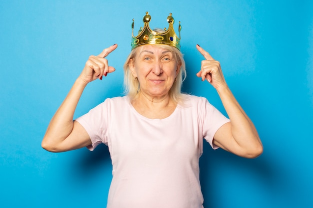 Portrait of an old friendly woman in a casual t-shirt with a crown on her head and points her fingers at the crown on an isolated blue wall. emotional face