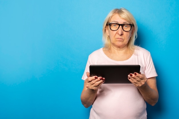 Portrait of an old friendly woman with a serious face in glasses and a casual t-shirt holding a tablet in her hands on an isolated blue wall. emotional face
