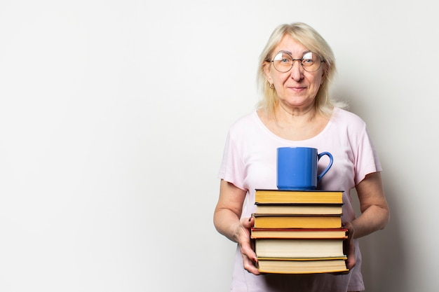 Portrait of an old friendly woman with a smile in a casual t-shirt and glasses holds a stack of books and a cup on an isolated light wall. emotional face. concept book club, leisure, education