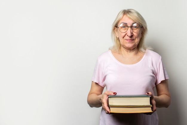 Portrait of an old friendly woman with smile in a casual t-shirt and glasses holds a stack of books on an isolated light wall. emotional face. concept book club, leisure, education