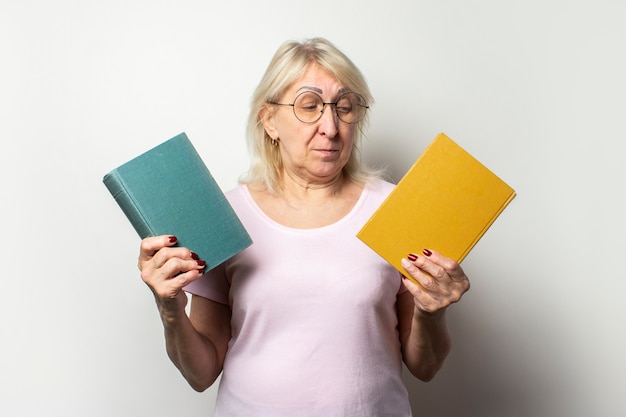 Portrait of an old friendly woman with a smile in a casual t-shirt and glasses holds two books on an isolated light wall. emotional face. concept book club, leisure, choice of books