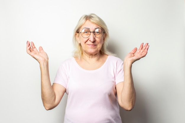 Portrait of an old friendly woman with a smile in a casual t-shirt and glasses shrug hands on an isolated light wall. emotional face. gesture of surprise, joy