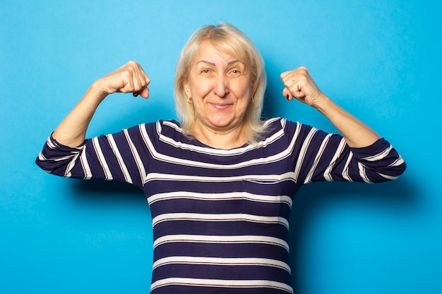 Portrait of an old friendly woman with a smile in a casual t-shirt makes a bodybuilder gesture on an isolated blue wall. emotional face. gesture strength, power, good health
