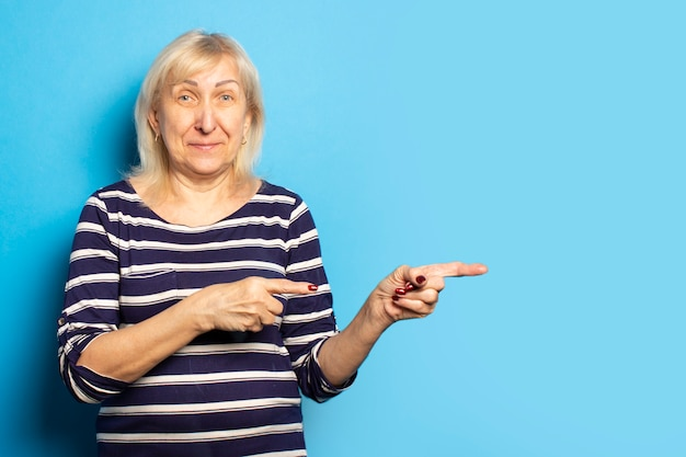 Portrait of an old friendly woman with a smile in a casual t-shirt points her hands to the side on an isolated blue wall. emotional face. gesture pay attention to it, look at it