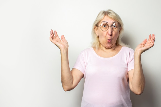 Portrait of an old friendly woman with a surprised face in a casual t-shirt and glasses shrug hands on an isolated light wall. emotional face. gesture of surprise, joy
